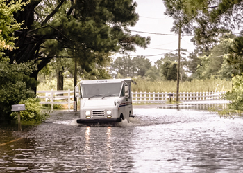 mail truck attempting to navigate flooded street