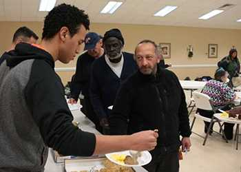 volunteers serving homeless people at winter shelter