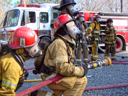 Firefighters with masks and hoses