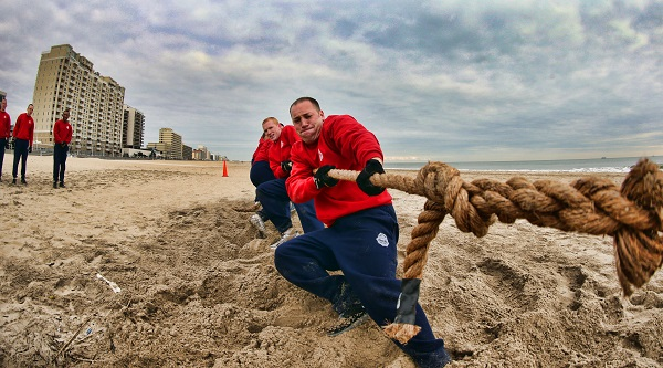 Firefighters pulling rope on beach