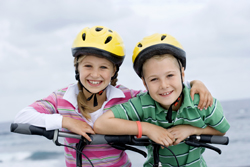 Boy and Girl at the beach with bikes wearing helmets